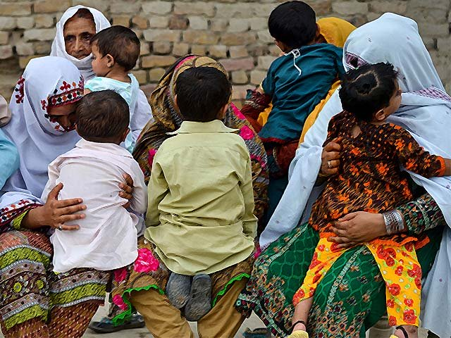 Women hold their children as they gather at a house at Wasayo village in Rato Dero in the district of Larkana, Pakistan. PHOTO: GETTY