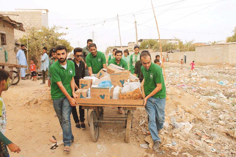 volunteers from the robin hood army in pakistan distributing food to the residents of bilal colony in karachi photo credit abbas mahmud