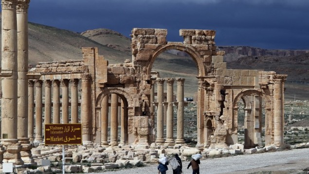 Syrians walking in the ancient oasis city of Palmyra on March 14, 2014. PHOTO: AFP
