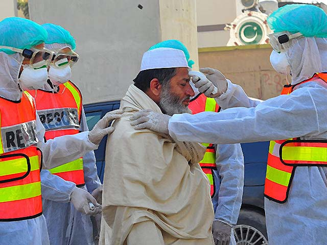 Pakistani rescue personnel check the body temperature of a man during a drill as a precaution against coronavirus. PHOTO: GETTY