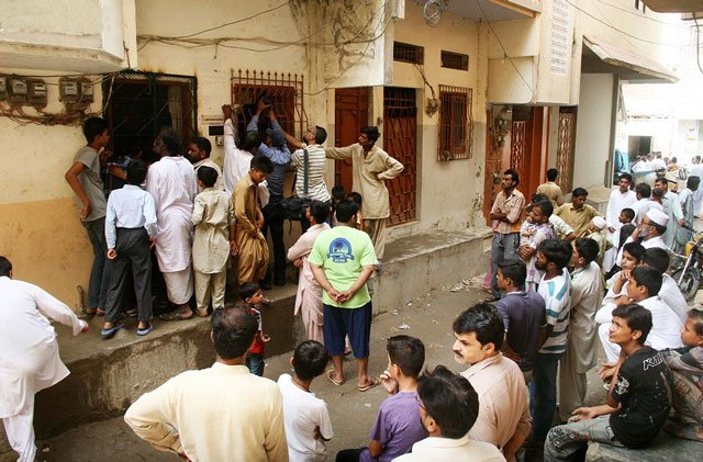 People gather outside a house in Karachi's Manzoor Colony area, where bodies of four family members were found on Wednesday September 09, 2015. PHOTO: ONLINE