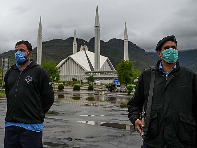 Policemen wearing face masks stand guard at a checkpoint beside the Grand Faisal Mosque during a government-imposed nationwide lockdown. PHOTO: GETTY