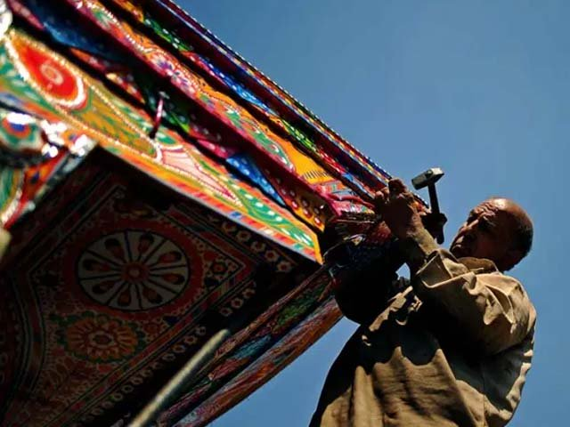 An electrician tacks electrical cables onto a decorated truck at a workshop in Rawalpindi. PHOTO: AFP
