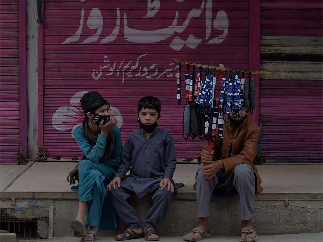 Children selling face masks wait for customers at a closed market area in Rawalpindi. PHOTO: AFP