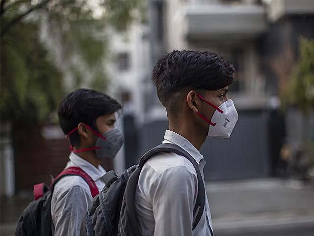 Boys wear protective masks as they walk back to their homes after school. PHOTO: AFP