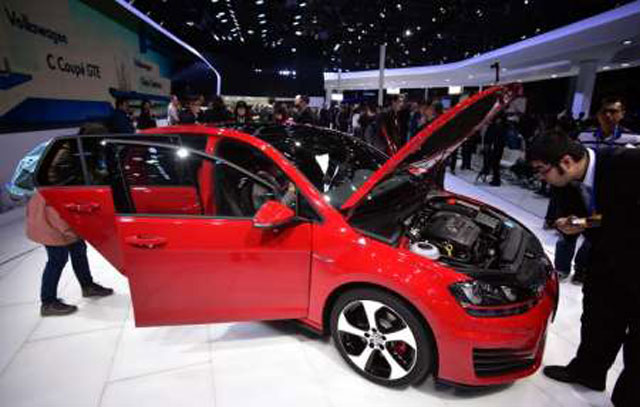 Journalists checkout a VW Golf GTI car on display at the 16th Shanghai International Automobile Industry Exhibition, on April 20, 2015. PHOTO: AFP