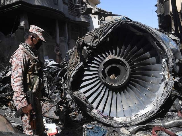 Security personnel stand beside the wreckage of the plane. PHOTO: AFP
