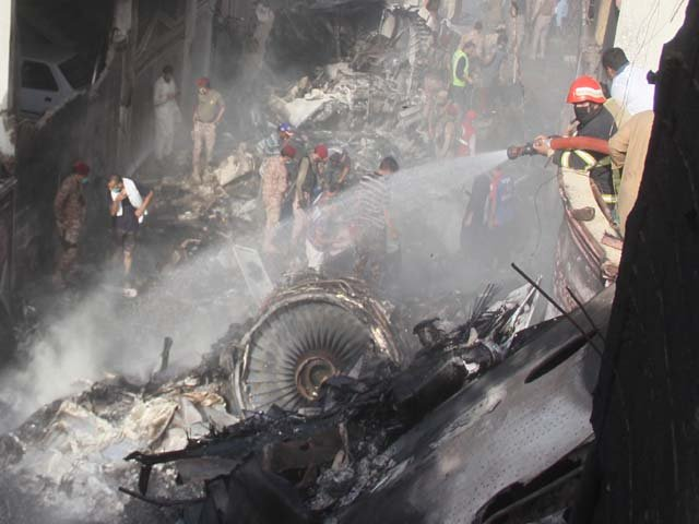 rescue workers gather at the site after a pia plane crashed photo afp