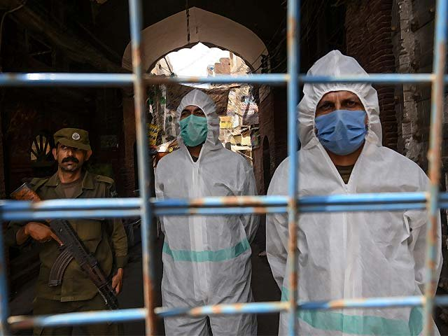 Policemen wearing gear stand guard behind a barricade at a restricted area sealed by the authorities in Lahore. PHOTO: AFP