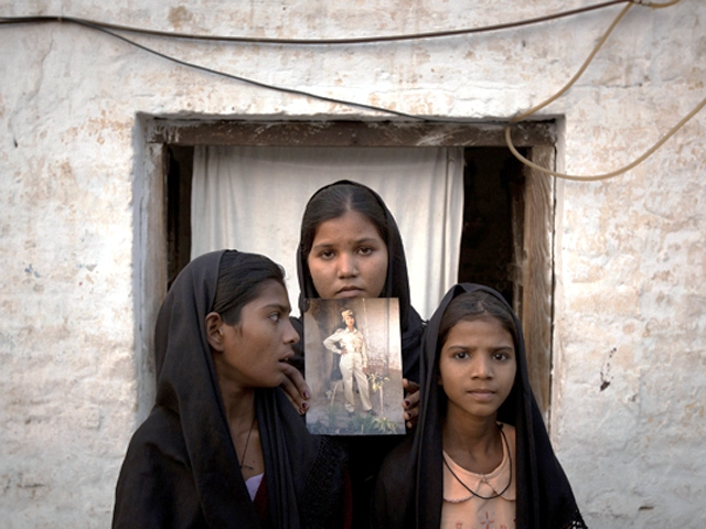 the daughters of asia bibi with an image of their mother standing outside their residence in sheikhupura on november 13 2010 photo reuters