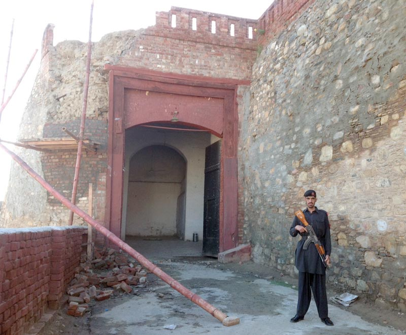 an fc soldier stands near the damaged shabqadar fort photos express