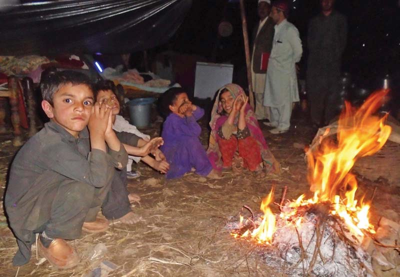 children sit besides a fire to keep themselves warm in a temporary shelter in lower dir photo inp