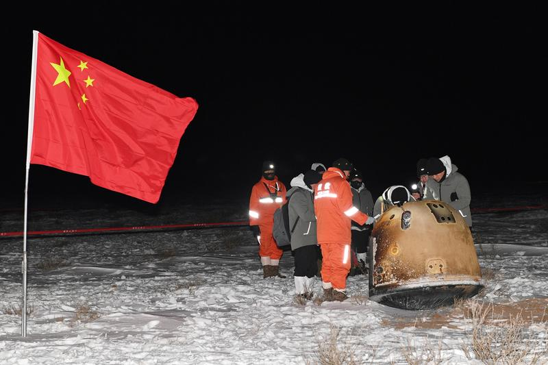 researchers work around chang e 5 lunar return capsule carrying moon samples next to a chinese national flag after it landed in northern china s inner mongolia autonomous region december 17 2020 photo reuters