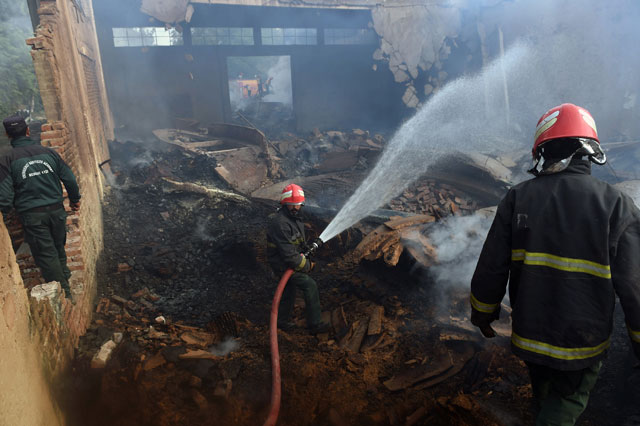 pakistani firefighters extinguish a fire at a factory after it was torched by an angry mob in jehlum on november 22 2015 photo afp