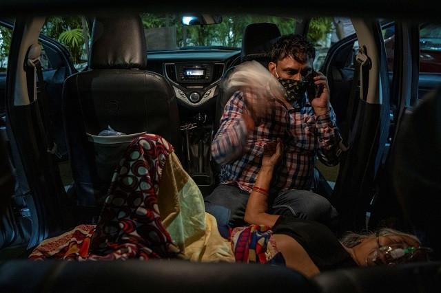 Manoj Kumar sits next to his mother, Vidhya Devi, who was suffering from a breathing problem as she receives oxygen support for free inside her car at a Gurudwara (Sikh temple), amidst the spread of the coronavirus disease (Covid-19), in Ghaziabad, India, April 24, 2021. PHOTO: REUTERS