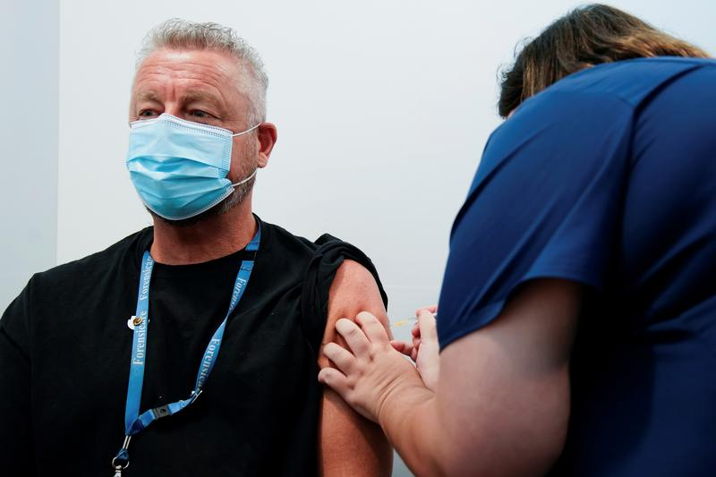 a healthcare professional administers a dose of the pfizer coronavirus disease covid 19 vaccine to dr chris quinn as high risk workers receive the first vaccines in the state of victoria s rollout of the program in melbourne australia february 22 2021 photo reuters