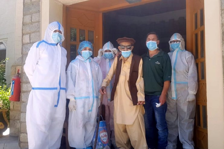 Abdul Alim, 103, stands with his son Suhail Aziz and staff members wearing PPE in this group photograph taken after he recovered from coronavirus. PHOTO: REUTERS