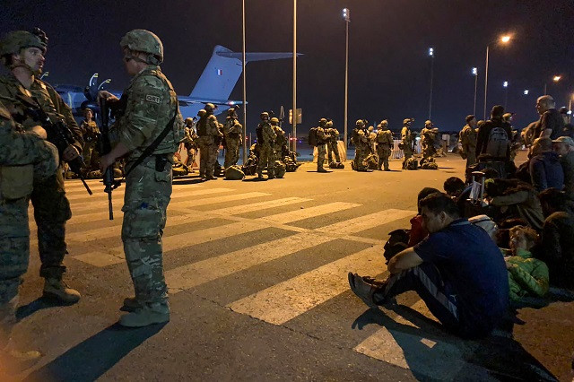 French soldiers stand guard as French nationals and their Afghan colleagues wait to board a military transport plane at the airport in Kabul. PHOTO: AFP