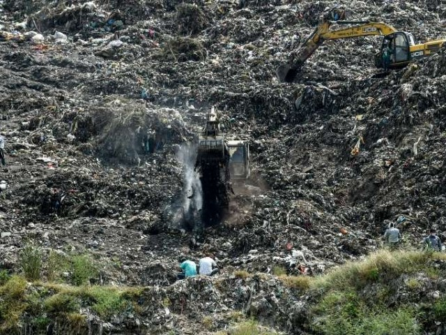 rescuers dig through indian trash dump for 12 year old rag picker