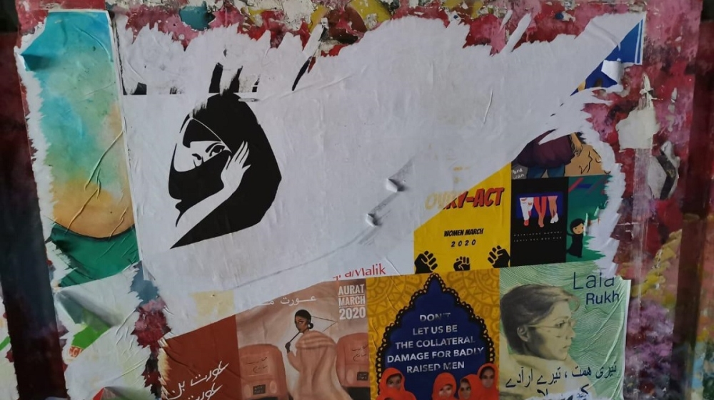 Photo: Vandalized poster of the Aurat March in Lahore [Amal Awais Chughtai/Al Jazeera]