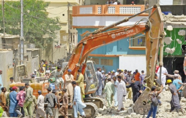 karachi metropolitan corporation workers use heavy machinery to tear down structures deemed illegal during an on going anti encroachment operation in orangi town photo online