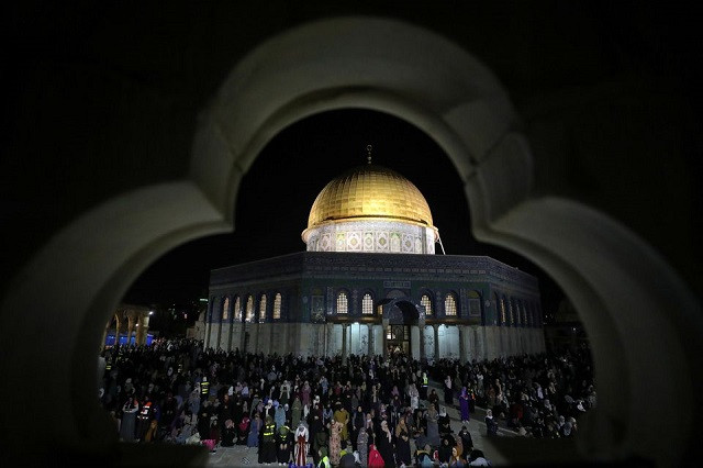 Palestinians pray in front of the Dome of the Rock on Laylat al-Qadr during the holy month of Ramazan, at the compound that houses Al-Aqsa Mosque, known to Muslims as Noble Sanctuary and to Jews as Temple Mount, in Jerusalem's Old City, May 8, 2021. PHOTO: REUTERS