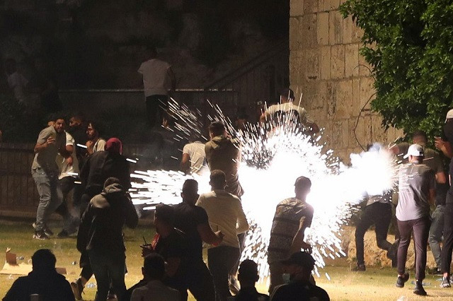 Palestinians react as Israeli police fire a stun grenade during clashes on Laylat al-Qadr during the holy month of Ramazan, at Jerusalem's Old City, May 8, 2021. PHOTO: REUTERS