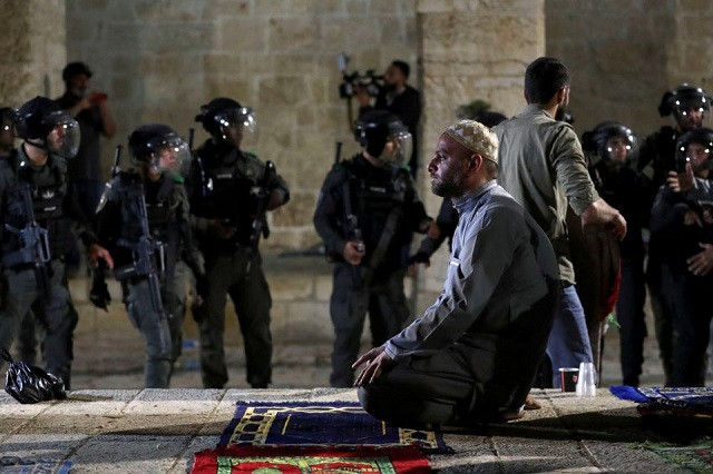 A Palestinian man prays as Israeli police gather during clashes at the compound that houses Al-Aqsa Mosque, known to Muslims as Noble Sanctuary and to Jews as Temple Mount, amid tension over the possible eviction of several Palestinian families from homes on land claimed by Jewish settlers in the Sheikh Jarrah neighbourhood, in Jerusalem's Old City, May 7, 2021. PHOTO: REUTERS