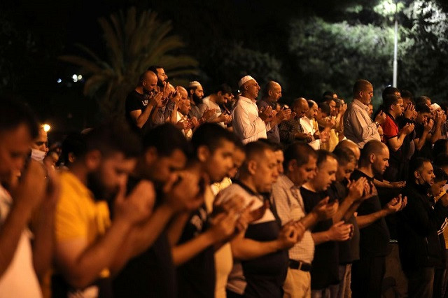 Palestinians pray on Laylat al-Qadr during the holy month of Ramazan, at the compound that houses Al-Aqsa Mosque, known to Muslims as Noble Sanctuary and to Jews as Temple Mount, in Jerusalem's Old City, May 8, 2021. PHOTO: REUTERS