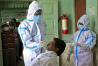 A healthcare worker wearing personal protective equipment (PPE) takes a swab from a man for a rapid antigen test as others wait for their turn at a check-up centre, amidst the spread of the Covid-19 in Kolkata, India. PHOTO: REUTERS/FILE