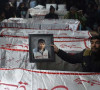 a mourner from the shia hazara community holds a photograph of a victim near the coffins of other miners who were killed in an attack by gunmen photo afp file