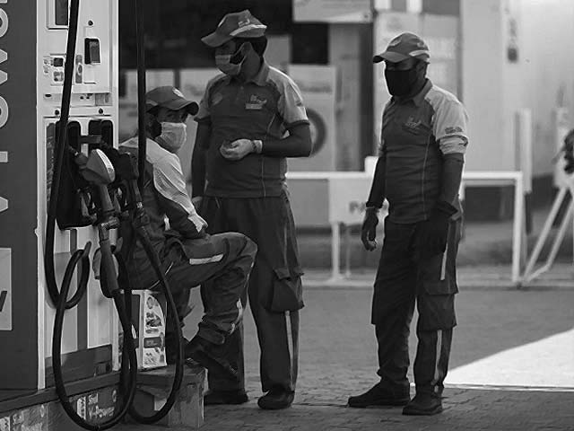 petrol station workers wearing face masks wait for customers photo afp