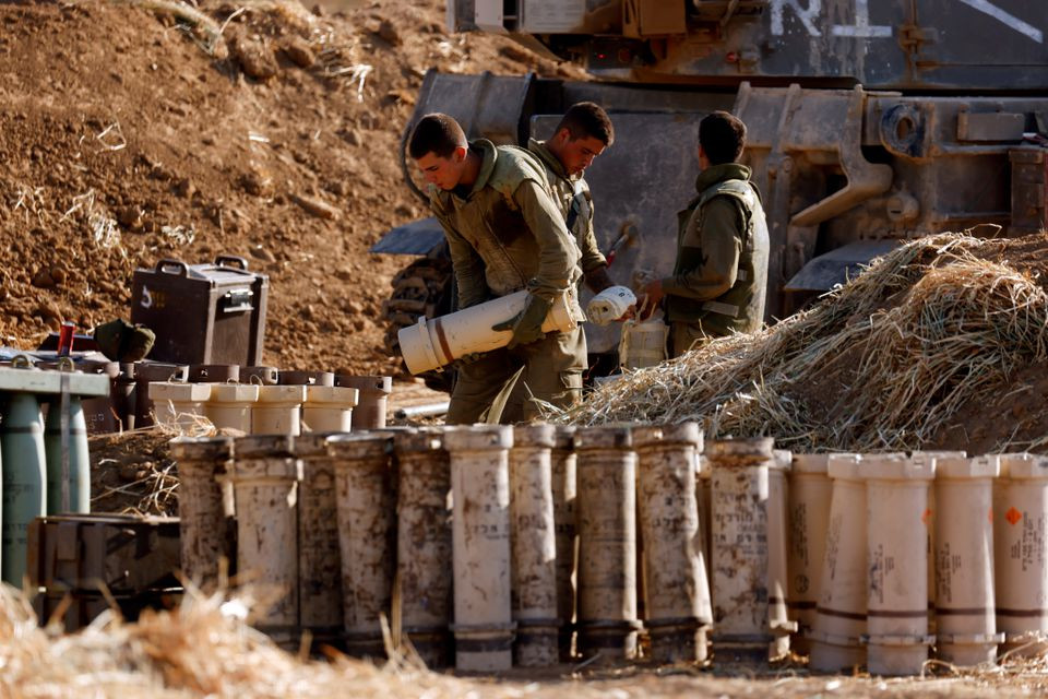 Israeli soldiers work by their mobile artillery unit near the border between Israel and the Gaza Strip. PHOTO: REUTERS