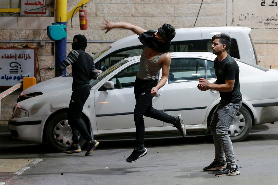 A Palestinian demonstrator hurls stones towards Israeli forces during an anti-Israel protest amid a flare-up of Israeli-Palestinian violence, in Hebron in the Israeli-occupied West Bank May 11, 2021. PHOTO: REUTERS