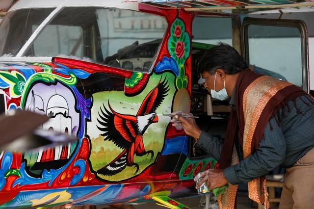 Painter Haider Ali, 40, paints Pakistani truck art on a two-seater Cessna aircraft at general aviation area at Jinnah International Airport in Karachi, Pakistan, December 30, 2020. PHOTO: REUTERS
