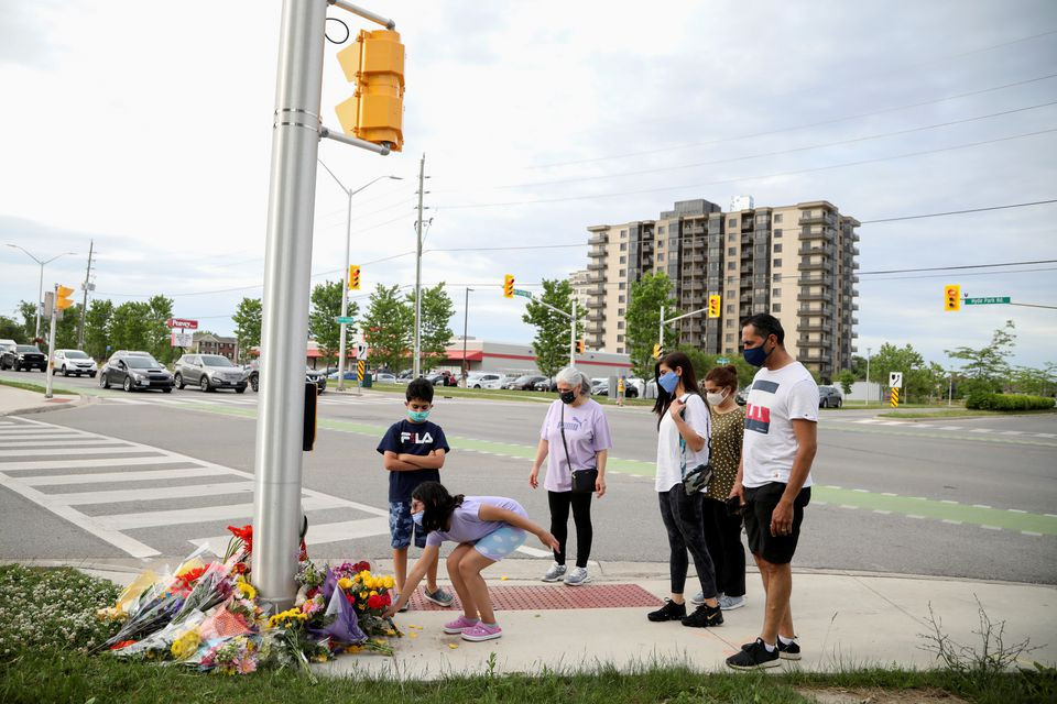 Members of the Selamati lay flowers at the fatal crime scene where a man driving a pickup truck jumped the curb and ran over a Muslim family in what police say was a deliberately targeted anti-Islamic hate crime, in London, Ontario, Canada June 7, 2021. PHOTO: REUTERS