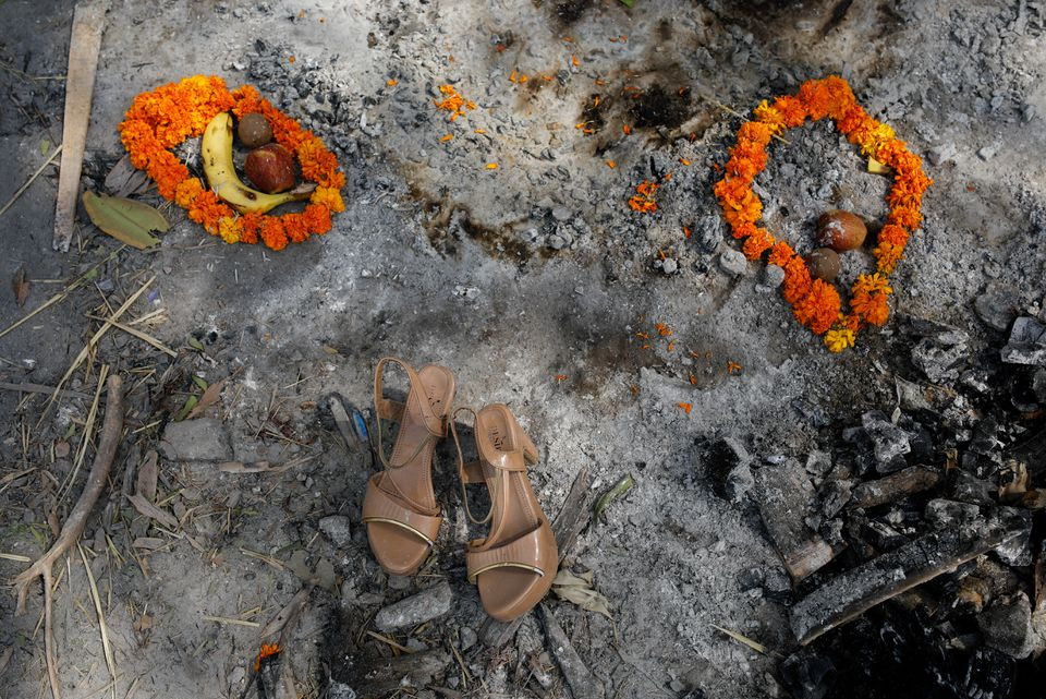 Flower garlands, fruits and a pair of sandals of a woman who died from the coronavirus disease (COVID-19), are placed by her relatives on the spot where she was cremated, as part of a ritual at a crematorium in New Delhi, India, April 30, 2021. REUTERS