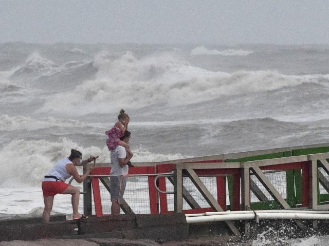 a girl covers her face from strong winds as her family members watch high swells from hurricane hanna from a jetty in galveston texas us july 25 2020 photo reuters file
