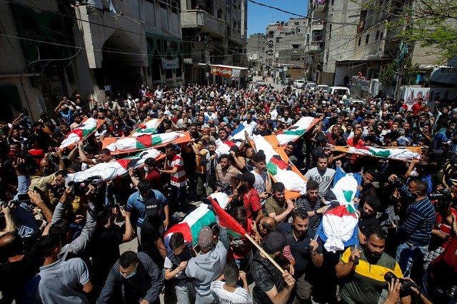 Mourners carry the bodies of Palestinians, including members of Abu Hatab family, who were killed amid a flare-up of Israeli-Palestinian violence, during their funeral at the Beach refugee camp, in Gaza City May 15, 2021. PHOTO: REUTERS