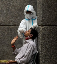 a-healthcare-worker-wearing-personal-protective-equipment-ppe-collects-a-swab-sample-from-a-man-amidst-the-spread-of-the-coronavirus-disease-covid-19-at-a-testing-center-in-new-delhi-india-october-29-2020-photo-reuters