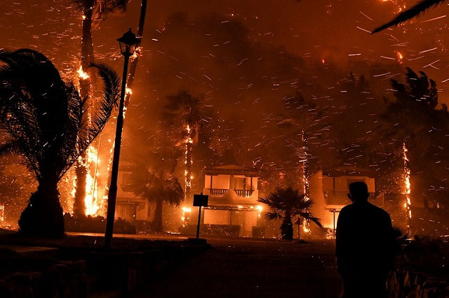 A local looks at flame rising among houses as a wildfire burns in the village of Schinos, near Corinth, Greece, May 19, 2021. PHOTO: REUTERS