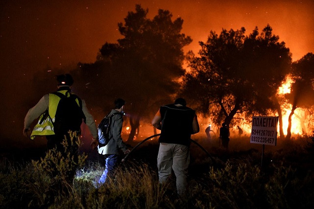 Firefighters and volunteers try to extinguish a wildfire burning in the village of Schinos, near Corinth, Greece, May 19, 2021. PHOTO: REUTERS