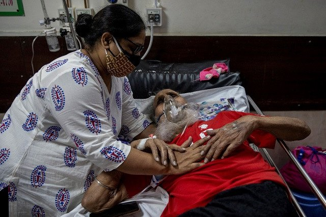 a man suffering from the coronavirus disease covid 19 is comforted by his daughter as he receives treatment inside the casualty ward at a hospital in new delhi india may 1 2021 photo reuters
