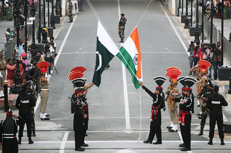 pakistani rangers wearing black uniforms and indian border security force bsf officers lower their national flags during parade on the pakistan s 72nd independence day at the pakistan india joint check post at wagah border near lahore photo reuters file