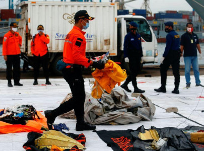 indonesia names first plane crash victim steps up black box hunt