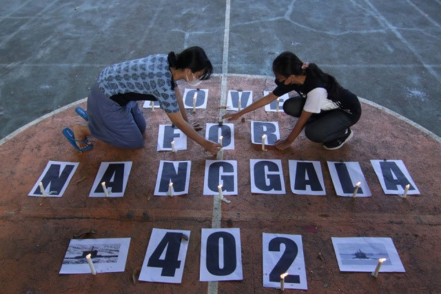 Students arrange the candles during a vigil for crew members who onboard the submarine KRI-402, sunk at the north Bali sea during a drill, in Banyuwangi, East Java province, Indonesia, April 27, 2021. PHOTO: REUTERS