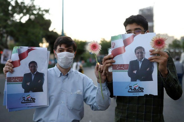 Supporters of presidential candidate Abdolnaser Hemmati hold posters of him in a street in Tehran, Iran June 16, 2021. PHOTO: REUTERS