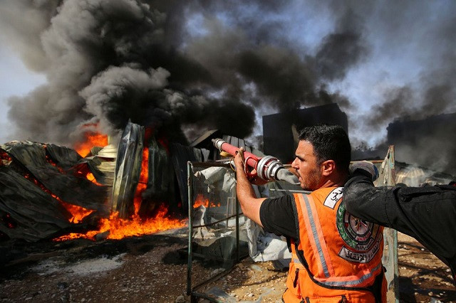 A Palestinian firefighter participates in efforts to put out a fire at a sponge factory after it was hit by Israeli artillery shells, according to witnesses, in the northern Gaza Strip May 17, 2021. PHOTO: REUTERS