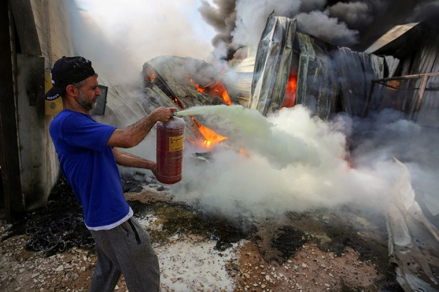A Palestinian man puts out a fire at a sponge factory after it was hit by Israeli artillery shells, according to witnesses, in the northern Gaza Strip May 17, 2021. PHOTO: REUTERS