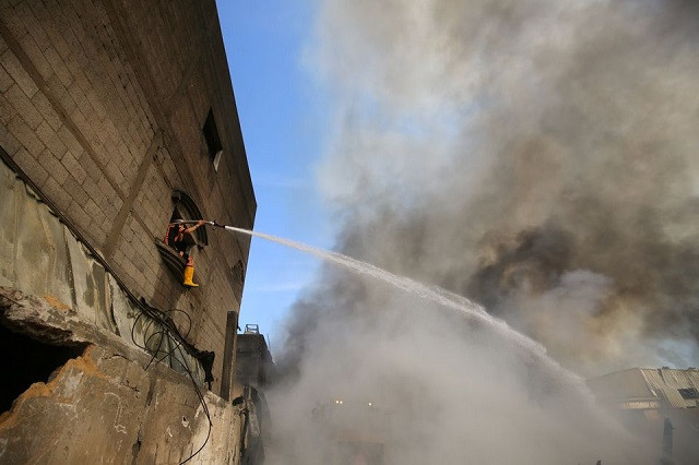 A Palestinian firefighter puts out a fire at a sponge factory after it was hit by Israeli artillery shells, according to witnesses, in the northern Gaza Strip May 17, 2021. PHOTO: REUTERS